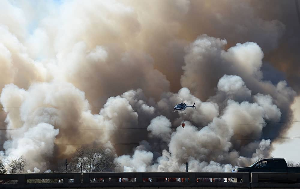 A helicopter flies past plumes of smoke during firefighting efforts on a train trestle parallel to Interstate 10 near the Bonnet Carre Spillway, west of New Orleans.