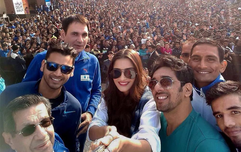 Bollywood actress Sonam Kapoor with Indian Olympians taking selfie before flagging off walk for heath initiative in New Delhi.