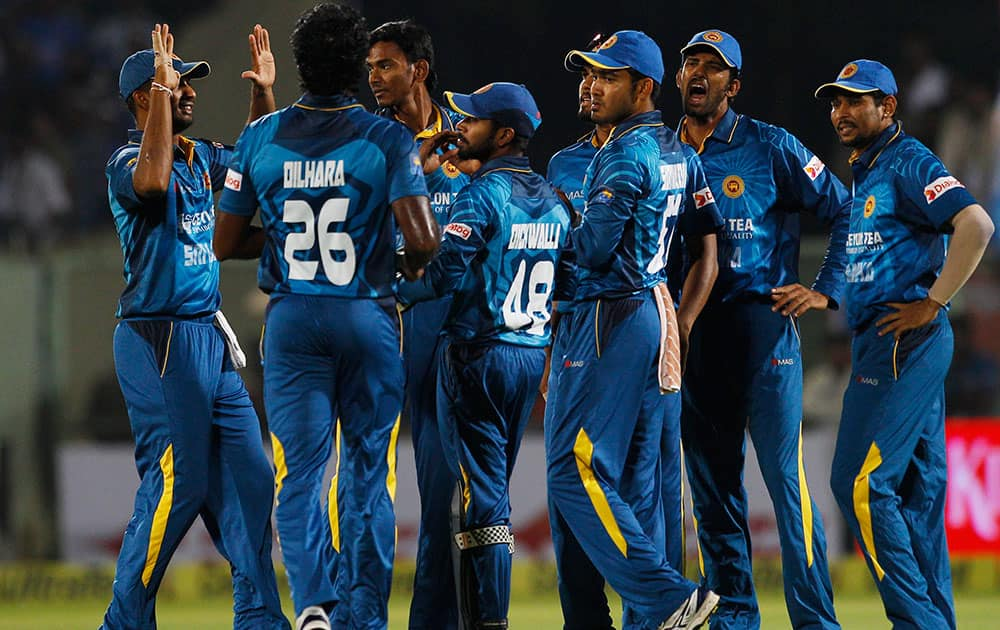 Sri Lankan players celebrate the dismissal of India's batsman Rohit Sharma during their third Twenty20 cricket match, in Vishakapatnam.