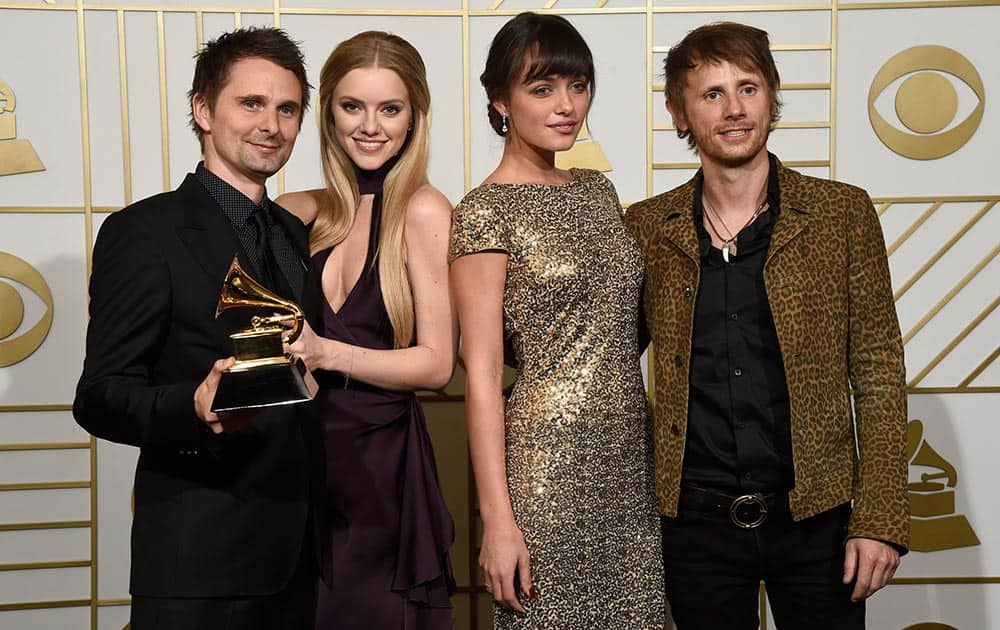 Matt Bellamy and Dominic Howard, right of Muse pose in the press room with the award for best rock album for 'Drones' along with Elle Evans, second left and Rayana Ragan, second right at the 58th annual Grammy Awards at the Staples Center, in Los Angeles.