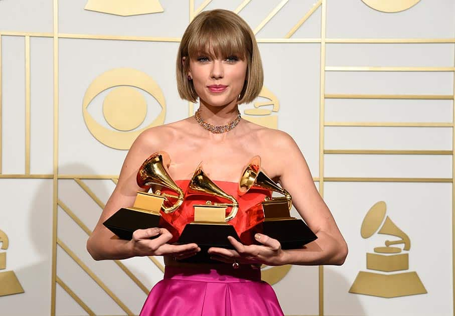Taylor Swift poses in the press room with the awards for album of the year for 1989, pop vocal album for 1989 and best music video for 'Bad Blood' at the 58th annual Grammy Awards at the Staples Center, in Los Angeles.