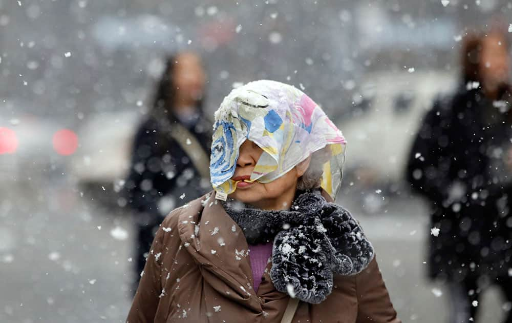 A woman covers her head with a scarf against heavy snow in Seoul, South Korea.