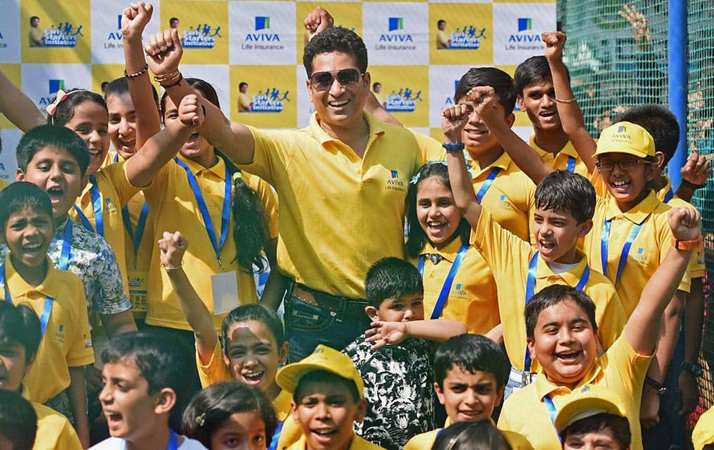 Cricket legend Sachin Tendulkar with kids during a promotional event of Aviva Life Insurance in Mumbai.