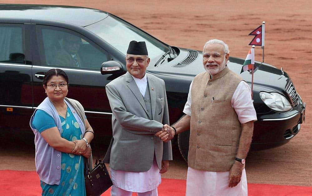 Prime Minister Narendra Modi greets his Nepalese counterpart Khadga Prasad Sharma Oli as his wife Radhika Shakya looks on during a ceremonial reception at Rashtrapati Bhavan in New Delhi.