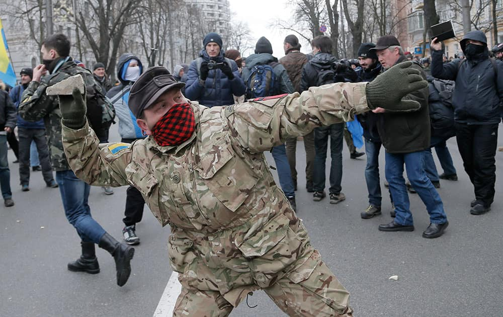 An ultra-right activist prepares to throw a stone towards a window of Sberbank of Russia office in Kiev, Ukraine.