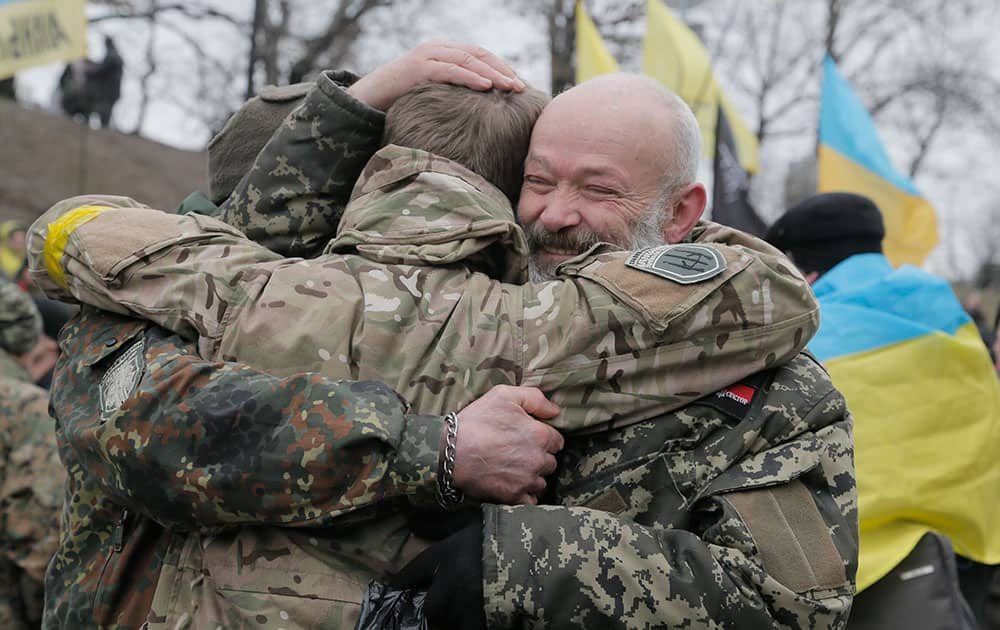 Soldiers of a volunteer battalion hug each during their unexpected meeting on Independence Square in Kiev, Ukraine.