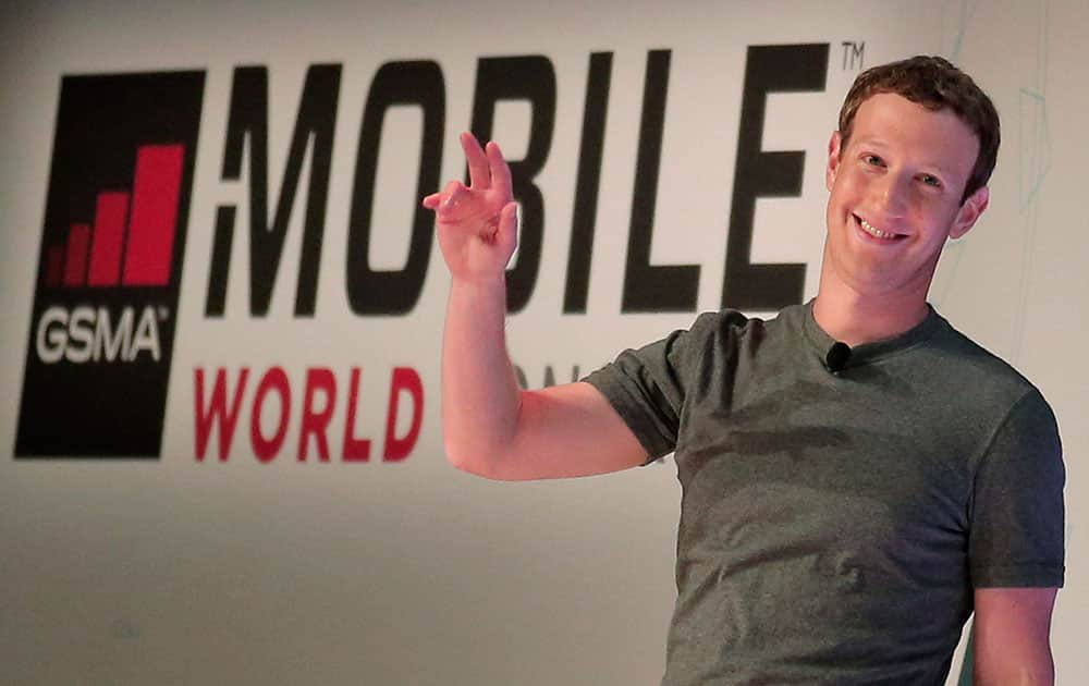 Facebook CEO Mark Zuckerberg waves to the audience as he arrives for a conference at the Mobile World Congress wireless show in Barcelona.