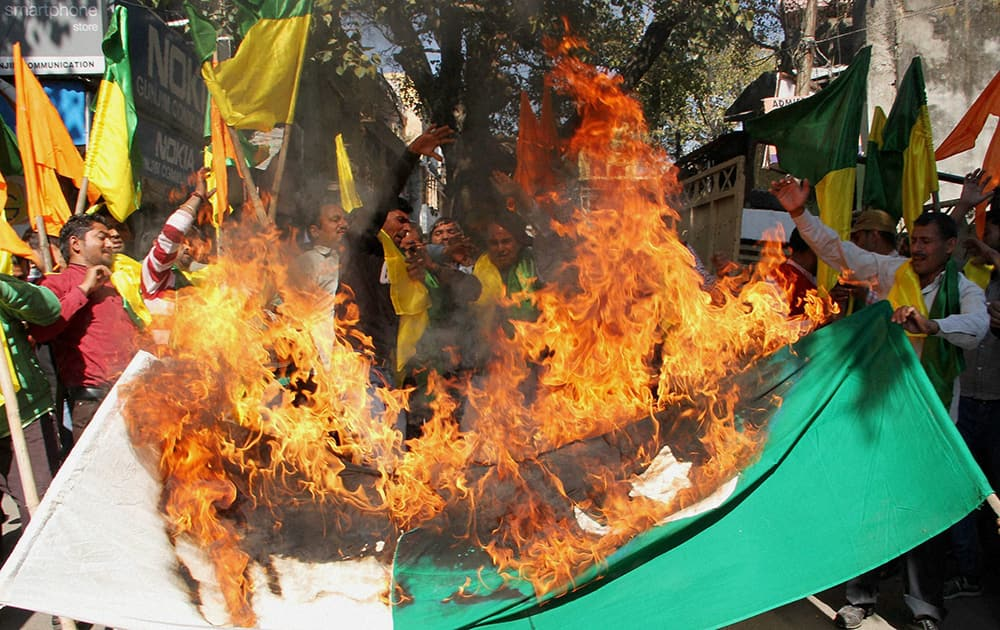 Activists of Jammu and Kashmir Dogra Front burn a flag of Paksitan during a protest in Jammu.