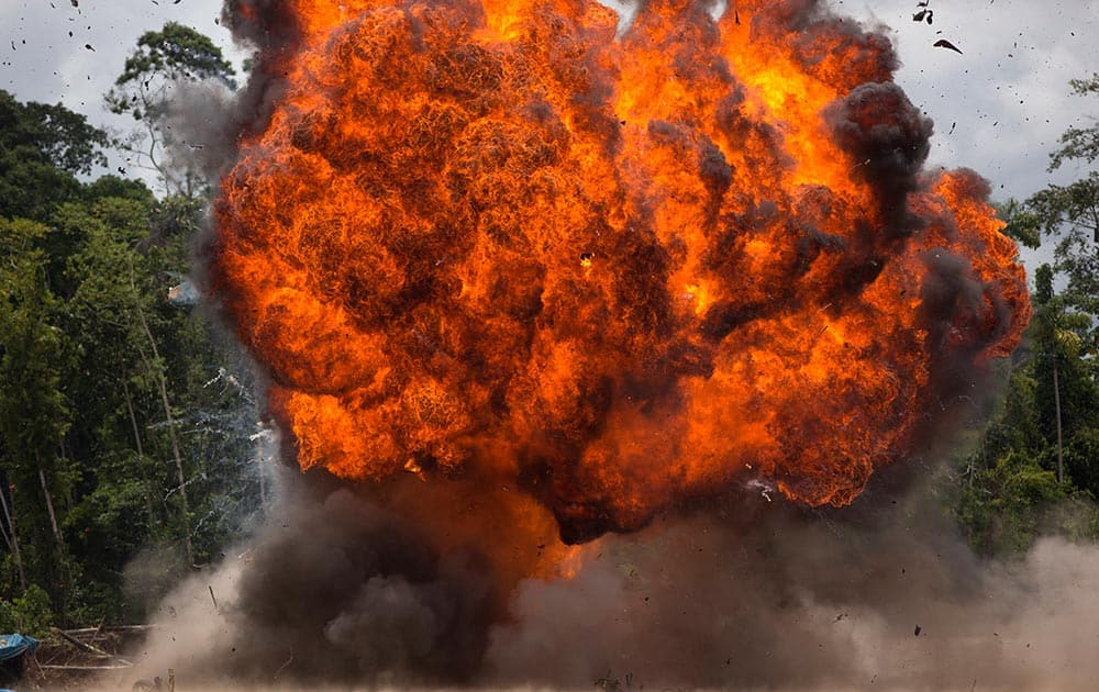 A fire ball rages after police set fire to motorcycles and gasoline at an illegal gold mining camp during a government raid to dismantle it in La Pampa.