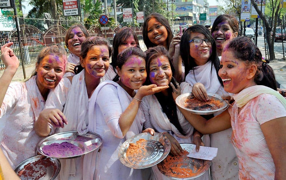 Students of Cotton College State University play Holi at a cultural procession during the University Week celebrations, in Guwahati.