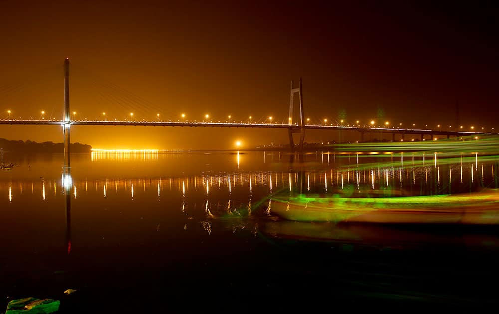 The bridge across the River Yamuna stands illuminated at night in Allahabad, India.