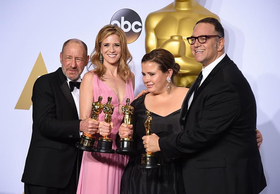 """Steve Golin, from left, Blye Pagon Faust, Nicole Rocklin and Michael Sugar, winners of the award for best picture for """"Spotlight"""" pose in the press room at the Oscars at the Dolby Theatre in Los Angeles."""