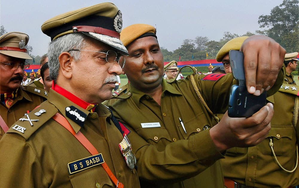 A policeman takes selfie with outgoing Delhi Police Commissioner BS Bassi at his farewell parade at New Police Lines in New Delhi.
