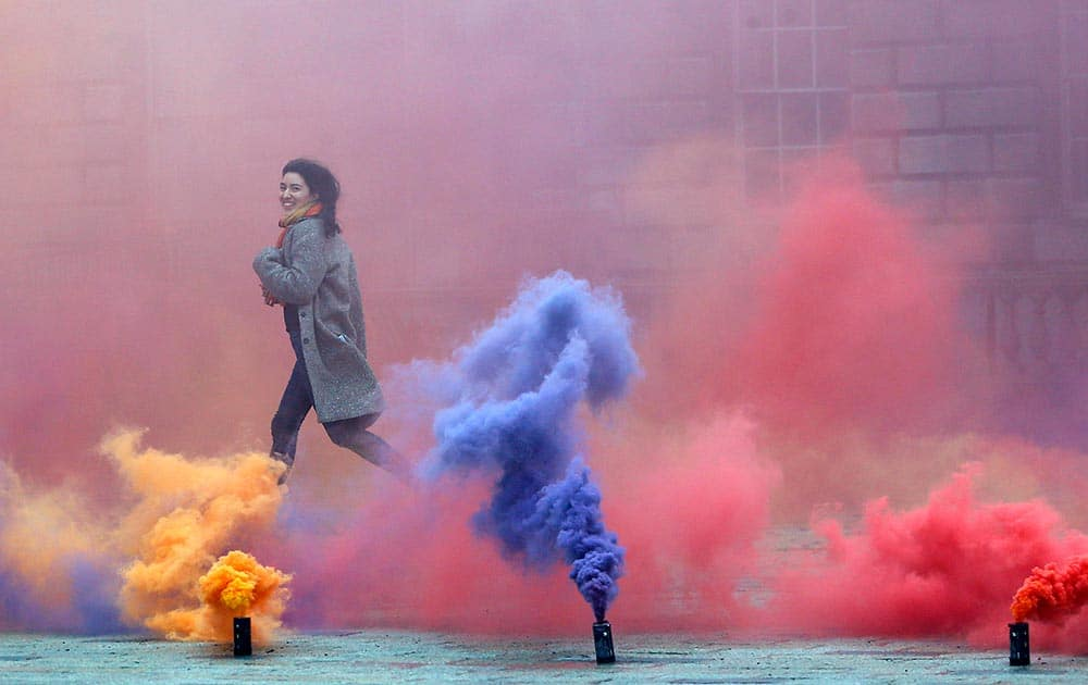 A woman runs through an artwork created by artist Filippo Minelli, a new work in his series Silence/Shapes, for the piece he let off colourful smoke bombs in Somerset House's courtyard, in London.