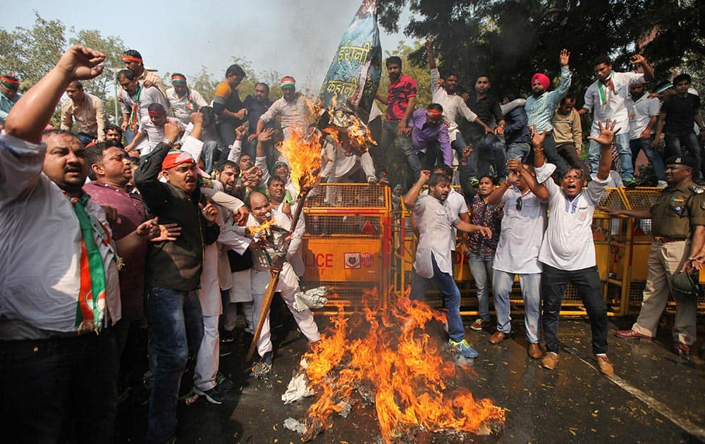 Supporters of the youth wing of India's opposition Congress Party burn the effigy of Human Resource Development Minister Smriti Irani during a protest in New Delhi.