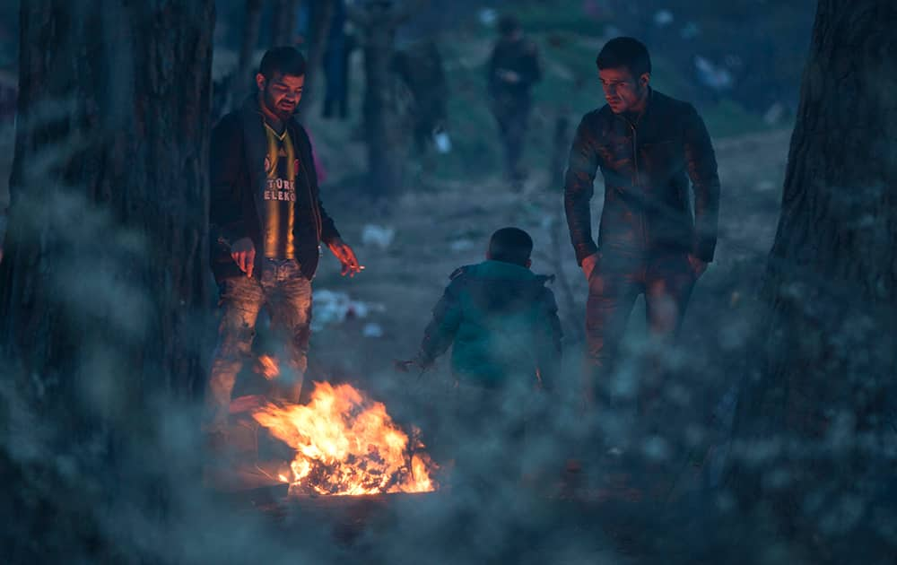 Migrants gather around a fire to keep warm while stranded on the Greek side of the border to enter Macedonia near the southern Macedonian town of Gevgelija.