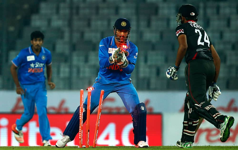 Mahendra Dhoni, center, takes the wicket of United Arab Emirates' Farhan Ahmed, right, during the Asia Cup Twenty20 international cricket match between them in Dhaka.