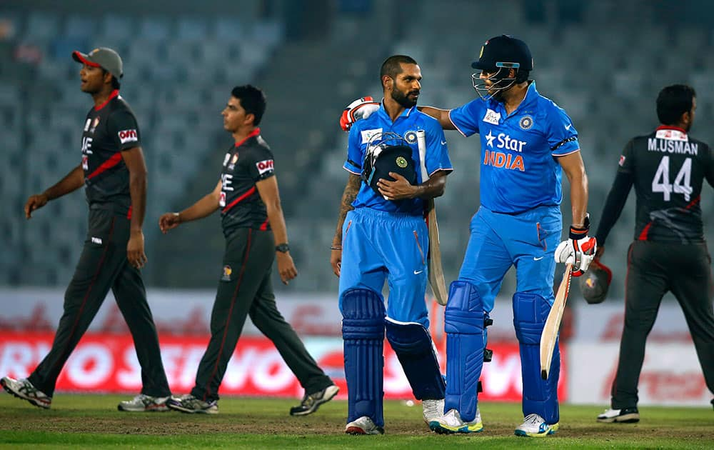 Shikhar Dhawan and Yuvraj Singh, walk out from the field after winning the Asia Cup Twenty20 international cricket match against United Arab Emirates in Dhaka, Bangladesh.