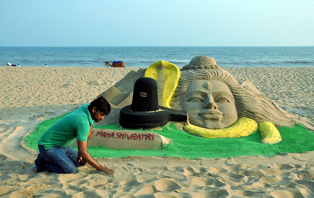 Sand artist Manas Kumar Sahoo prepared Lord Shivas sand sculpture on eve of Mahashivratri at Puri beach in Odhisa.