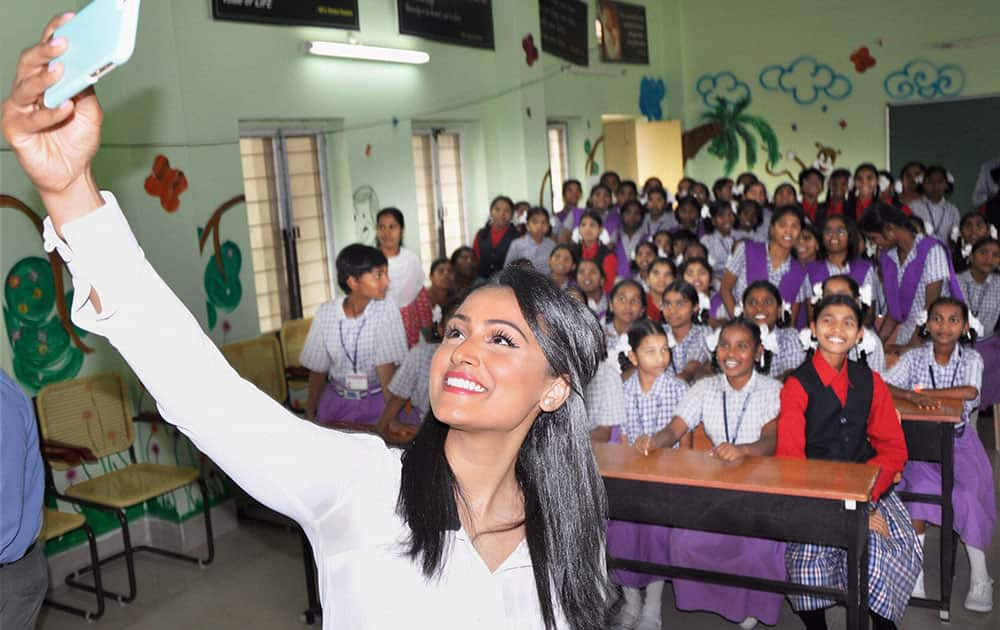 Miss USA 2014 Nina Davuluri takes a selfie with the kids of at a school in Hyderabad.
