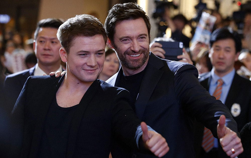 Actors Taron Egerton, left, and Hugh Jackman, right, pose for their fans during a red carpet event to promote their latest movie Eddie The Eagle in Seoul, South Korea.
