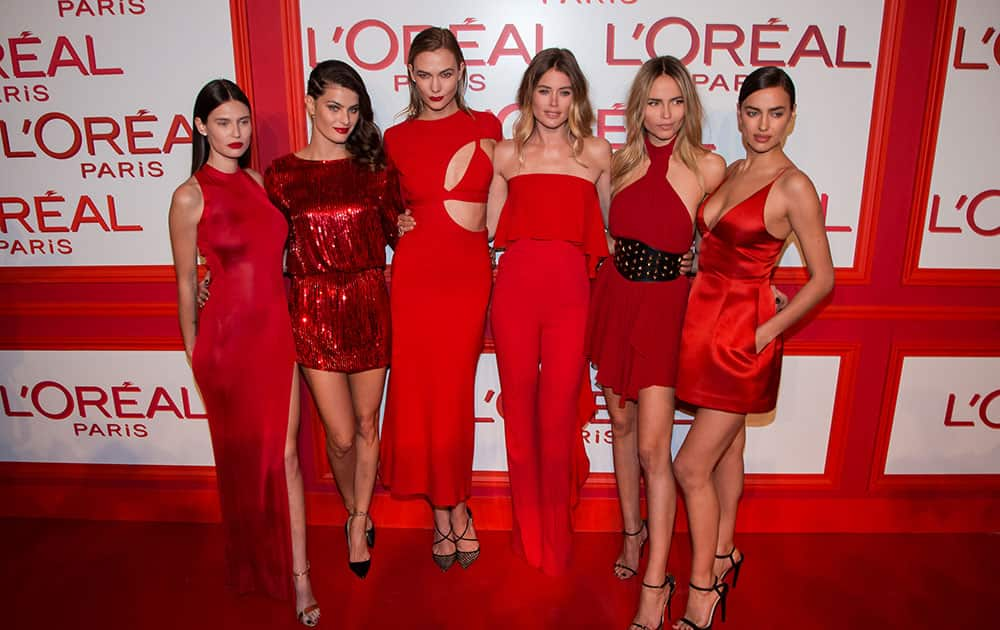 Models, from left, Bianca Balti, Isabeli Fontana, Karlie Kloss, Doutzen Kroes, Natasha Poly and Irina Shayk pose for photographers upon arrival at the L'Oreal Red Obsession Party in Paris.