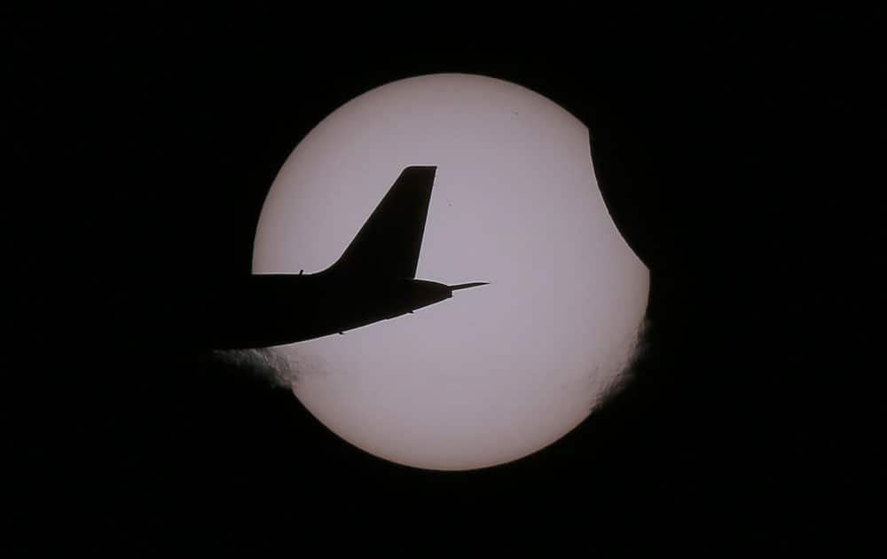 An Air Asia passenger plane flies as a partial solar eclipse occurs as seen from Taguig city, east of Manila, Philippines.