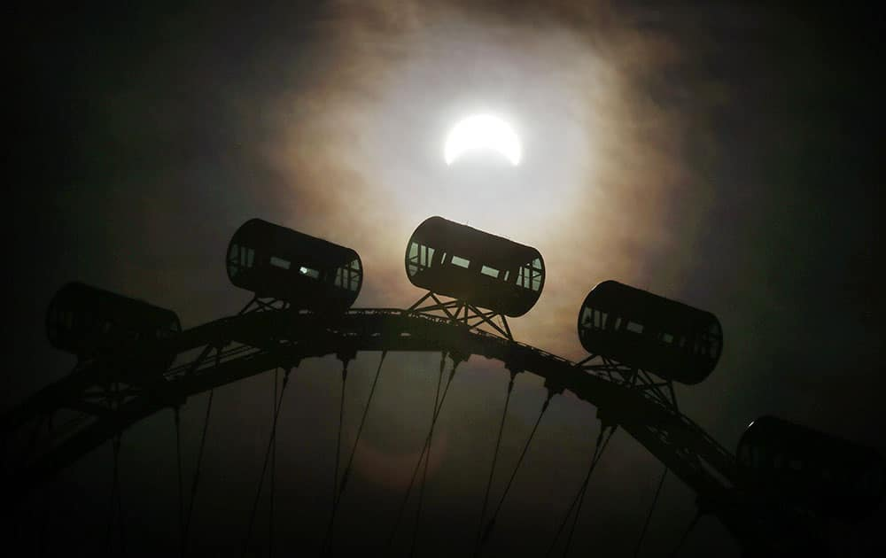 A partial solar eclipse is seen behind passenger capsules of the Singapore Flyer in Singapore.
