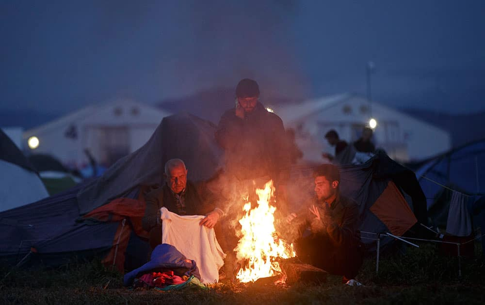 People dry clothes around a fire at the Greek border camp near Idomeni