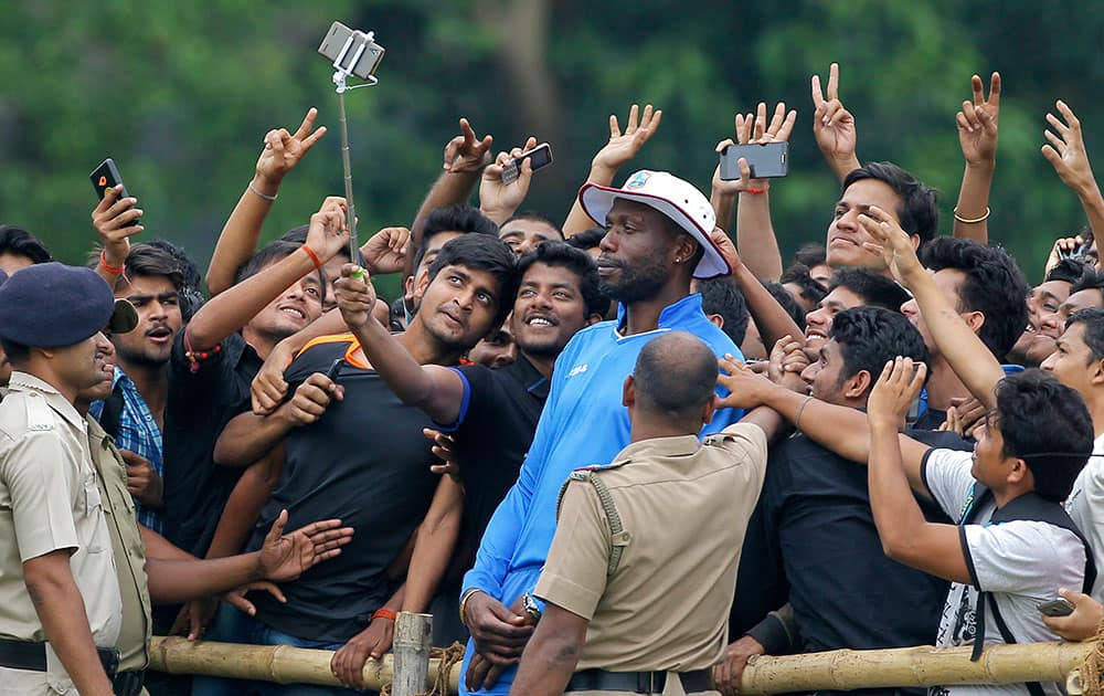 West Indies bowling coach Curtley Ambrose poses for a selfie with Indian fans during a training session prior to their practice match of the ICC World Twenty20 2016 cricket tournament in Kolkata.