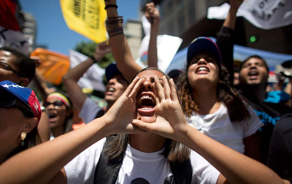 A woman cups her hands around her mouth as she shouts with others during an opposition protest in Caracas, Venezuela.