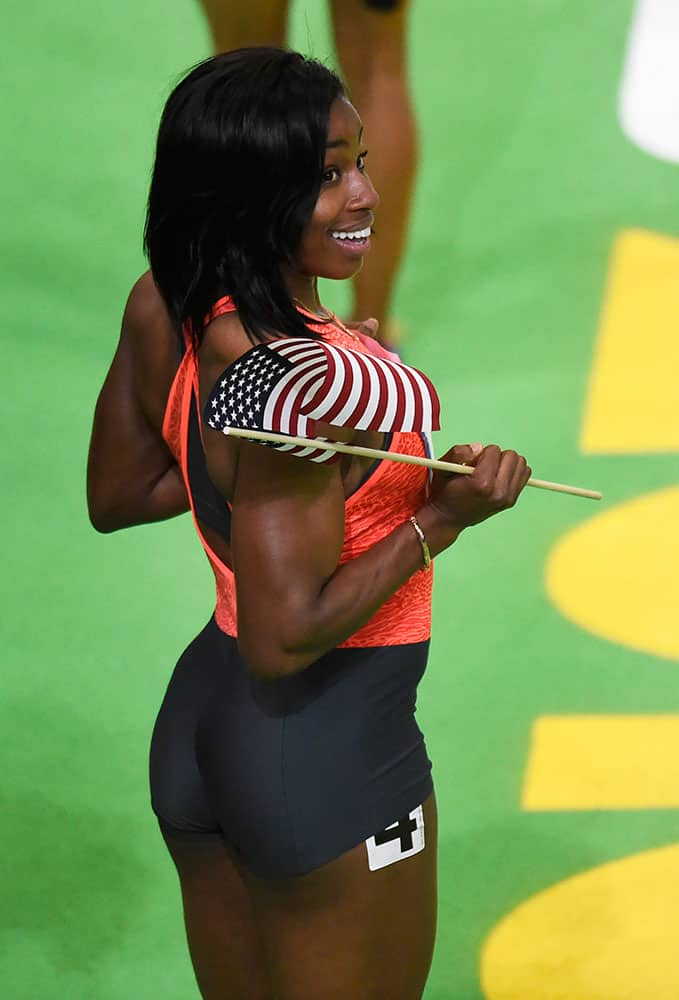 Barbara Pierre waves a U.S. flag after winning the women's 60 meters at the U.S. indoor track and field championships in Portland, Ore.