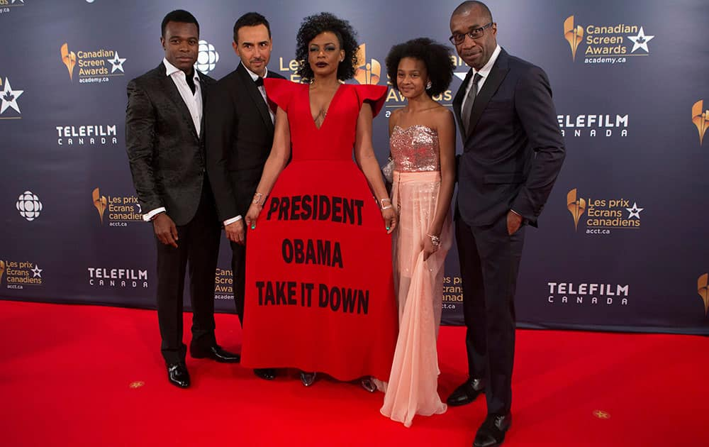 Aunjanue Ellis, centre, wears a dress with a slogan printed on it as a protest against the presence of the Confederate Flag on Capitol Hill, as she stands on the red carpet with cast members from the television show 'Book of Negroes' at the 2016 Canadian Screen Awards in Toronto.
