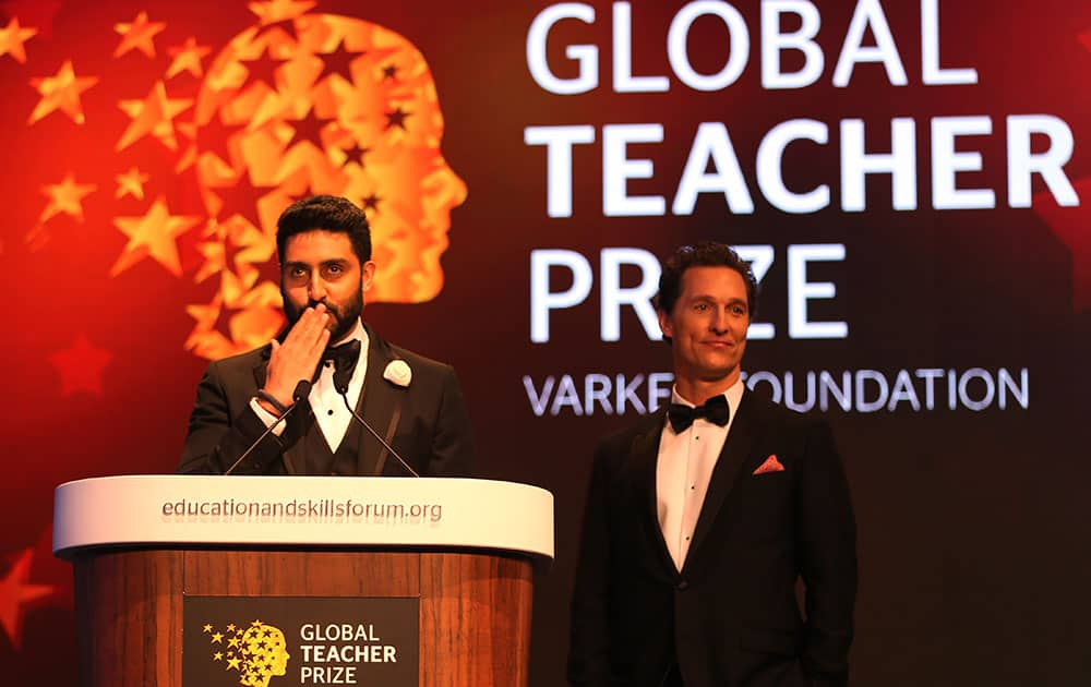 Bollywood actor Abhishek Bachchan, left stands next to Matthew McConaughey as he blows a kiss to the audience during a ceremony awarding the Global Teacher Prize, in Dubai, United Arab Emirates.