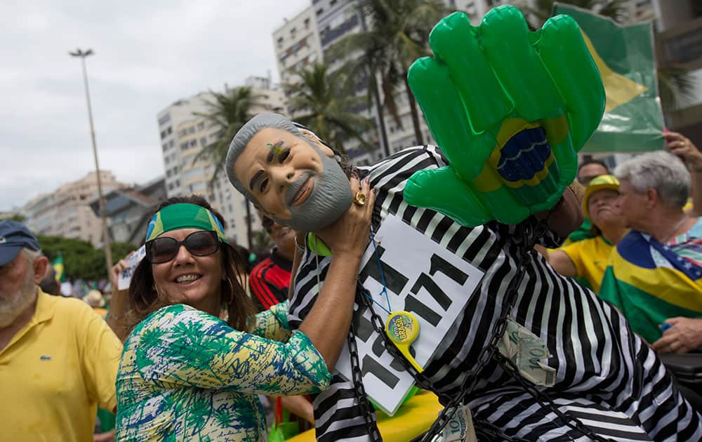 A demonstrator pretends to strangle an effigy of Brazil's former President Luiz Inacio Lula da Silva, wearing prison garb, during a protest demanding the impeachment of current President Dilma Rousseff in Rio de Janeiro, Brazil.