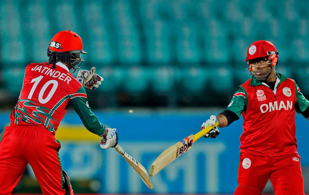 Oman's Amir Ali, right, and Jatinder Singh touch bats during the ICC World Twenty20 2016 cricket tournament against Bangladesh at the Himachal Pradesh Cricket Association (HPCA) stadium in Dharamsala.