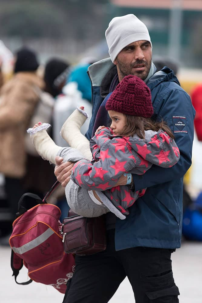 A Syrian man carries a child as migrants and refugees who just arrived with a ferry from Greek island prepare to get on busses with destination a transit camp at the port of Piraeus near Athen.