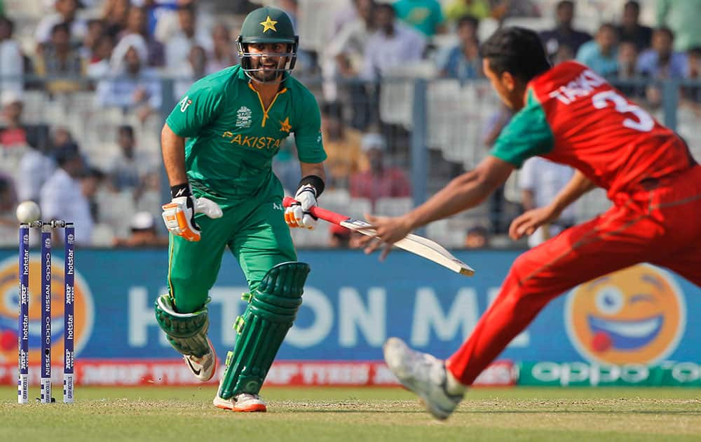 Pakistan's Ahmed Shehzad scores a run as Bangladesh's Taskin Ahmed tries to collect the ball during their match of the ICC World Twenty20 2016 cricket in Kolkata.