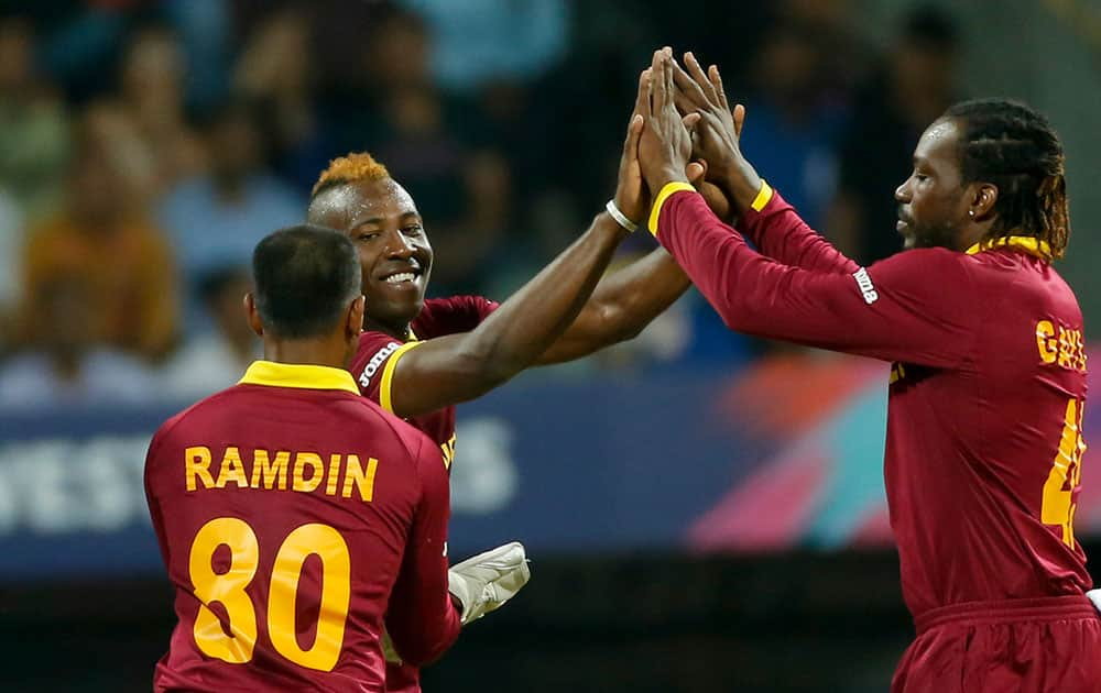 West Indies Andre Russell, left, celebrates the wicket of England's Jason Roy during their ICC World Twenty20 2016 cricket match at the Wankhede stadium in Mumbai.