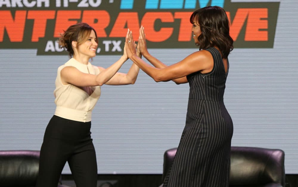 Actress Sophia Bush, left, and first lady Michelle Obama high-five at a panel discussion during South By Southwest at the Austin Convention Center in Austin, Texas.