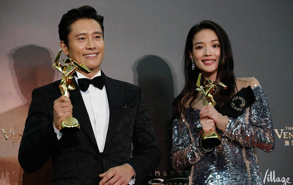 Taiwanese actress Shu Qi, right, and South Korean actor Lee Byung-hun pose after winning the Best Actress and Actor awards of the Asian Film Awards in Macau.