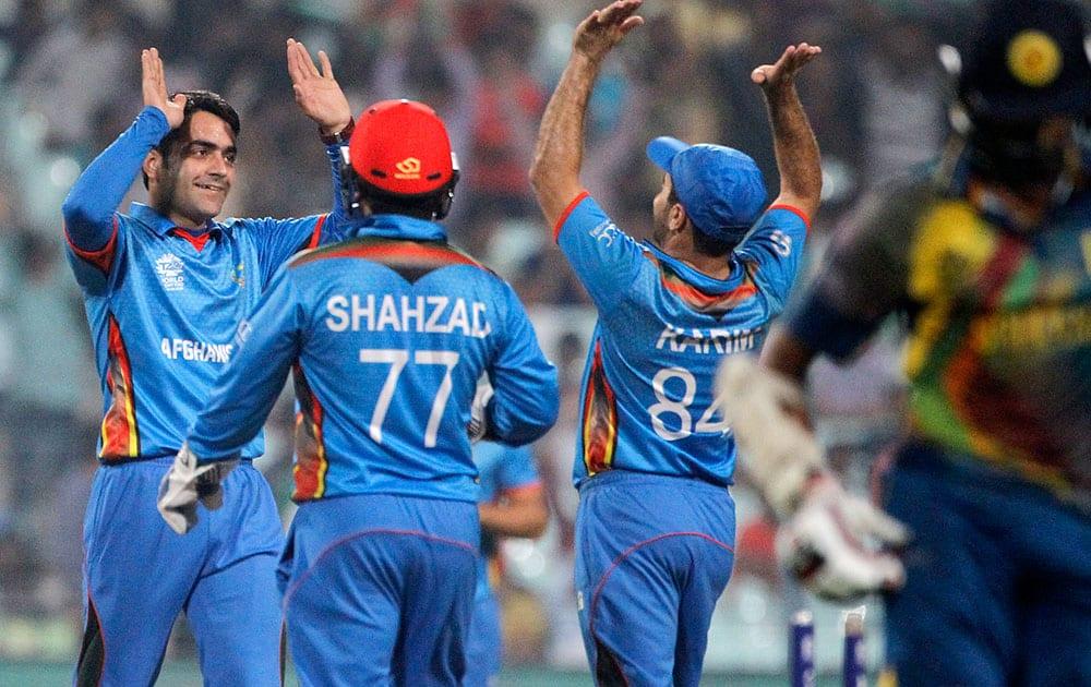 Afghanistan's Rashid Khan celebrates with teammates after the dismissal of Sri Lanka's Lahiru Thirimanne during their match of the ICC World Twenty20 2016 cricket tournament in Kolkata.
