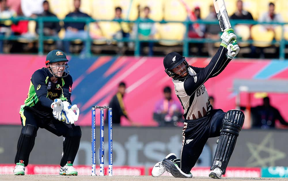 New Zealand's Martin Guptill hits a ball for six runs as Australia's Peter Nevill watches during the ICC World Twenty20 2016 cricket match at the Himachal Pradesh Cricket Association (HPCA) stadium in Dharamsala.