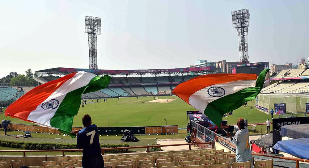 Indian cricket fans wave the national flags to show their support for the team, at the Eden Gardens in Kolkata.