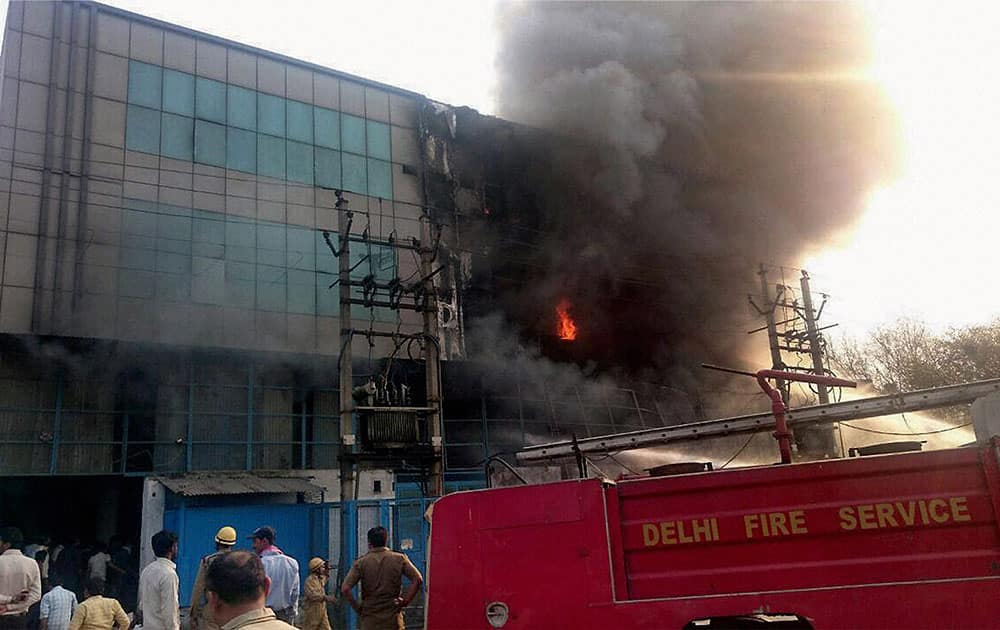 Fire personnel dousing a massive fire that broke out in a building in Mangolpuri in New Delhi.