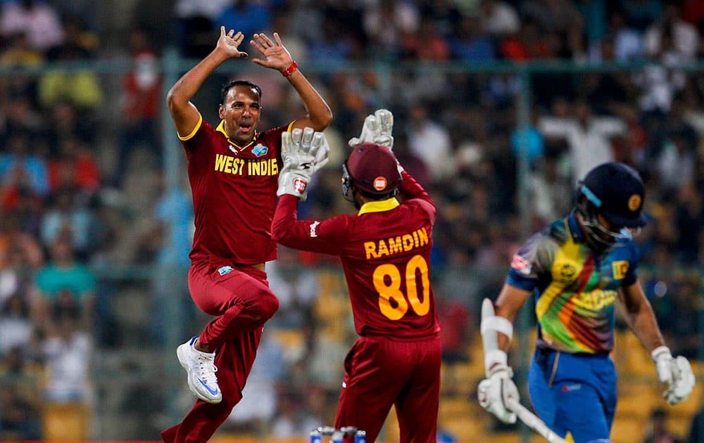 West Indies' Samuel Badree, left, celebrates after taking the wicket of Sri Lanka's Milinda Siriwardana, right, during their ICC World Twenty20 2016 cricket match in Bangalore.