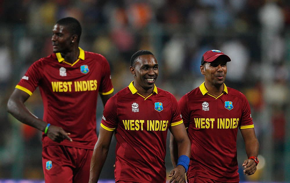 West Indies' Dwayne Bravo, center, leaves the field with teammates Samuel Badree, right, and Jason Holder at the end of the first innings during their ICC World Twenty20 2016 cricket match against Sri Lanka in Bangalore.