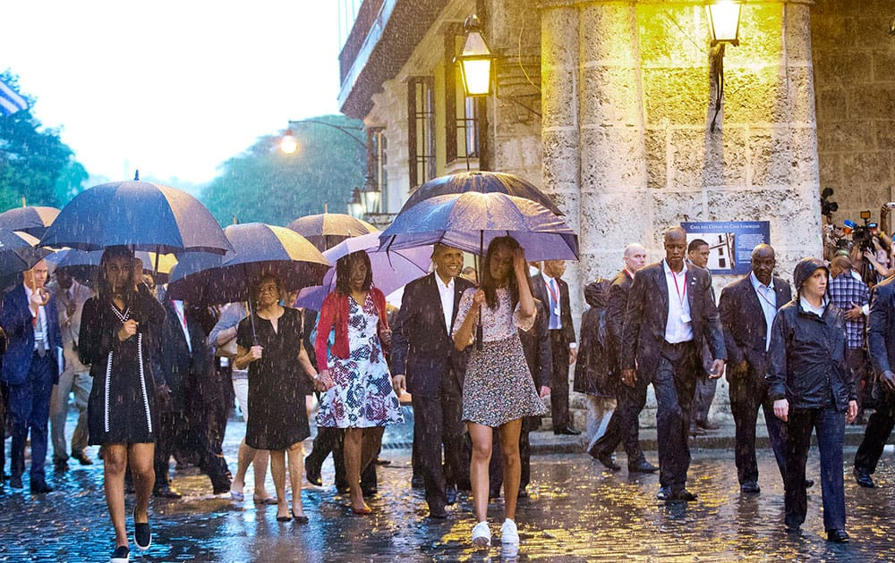 U.S. President Barack Obama, center, with his first lady Michelle Obama, daughters Malia and Sasha and first lady's mother Marian Robinson, take a walking tour of Old Havana in the rain, in Havana, Cuba.