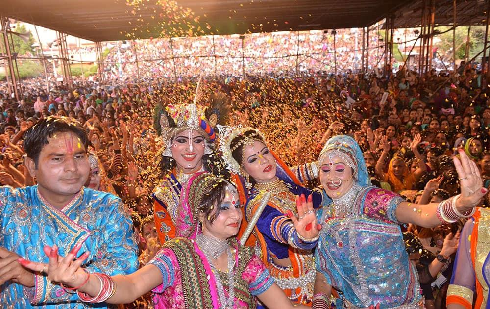 Artists dressed up as Lord Radha-Krishna, playing holi with flower petals during Latthmaar Holi celebration.