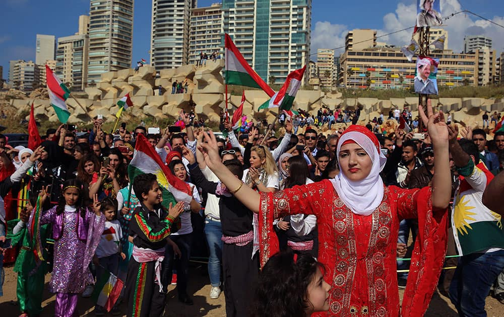 Kurdish citizens who live in Lebanon wear traditional clothes as they dance and wave Kurdish flags, during a celebration of Nowruz day, in Beirut, Lebanon.